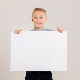 Ragazzo adorabile che tiene carta in bianco