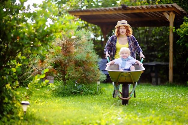 Ragazzo adorabile del bambino divertendosi in una carriola che spinge dalla mamma