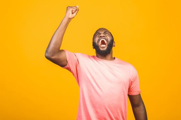 Ragazzo africano bello allegro che fa sì gesto mentre eccitato per la vittoria. estatico giovane tifo che tifa ed esprime sostegno. concetto di successo.
