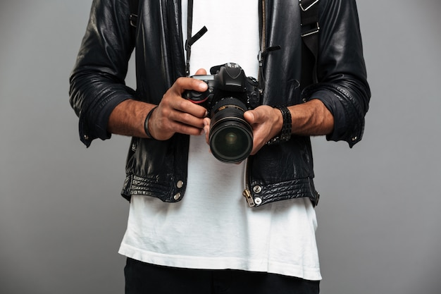 Ragazzo afroamericano alla moda che tiene macchina fotografica digitale