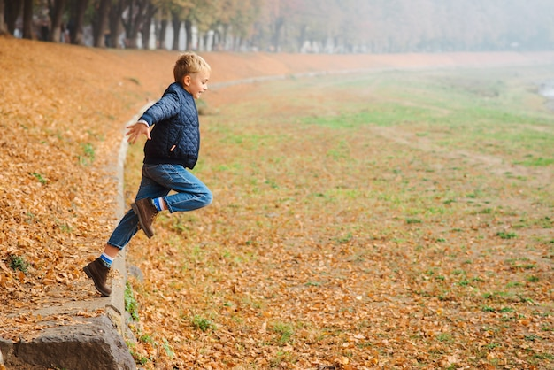 Ragazzo alla moda bello divertendosi all'aperto. bambino felice che salta sulla camminata di autunno. moda autunno. concetto di moda, famiglia e stagione autunnale