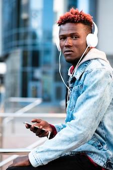 Ragazzo alla moda di medio colpo con cuffie e smartphone
