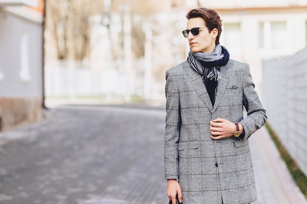 Ragazzo alla moda in occhiali da sole in cappotto con la cartella sulla strada
