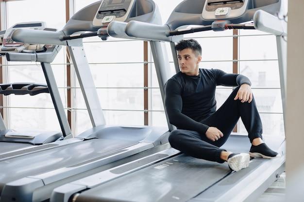 Ragazzo alla moda in palestra si siede a riposo sul tapis roulant. uno stile di vita sano.