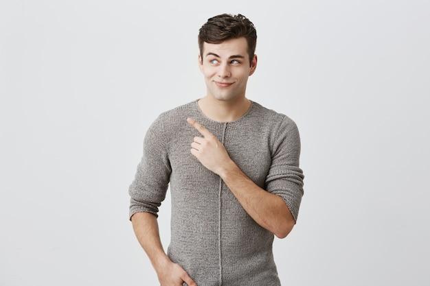 Ragazzo alla moda moro in maglione che guarda con i suoi occhi azzurri da parte che indica con il dito indice lo spazio della copia che fa pubblicità a qualcosa. equipaggi la posa contro la parete con lo spazio della copia per testo o la promozione