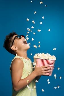 Ragazzo allegro con un secchio di popcorn, un sacco di popcorn cade dall'alto, il ragazzo lo cattura, divertimento e intrattenimento, il concetto di riposo