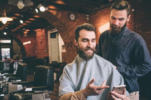 Ragazzo allegro e barbuto è seduto su una sedia e sorridente. sta mostrando una foto al suo parrucchiere. il parrucchiere è pronto a fare il suo lavoro.