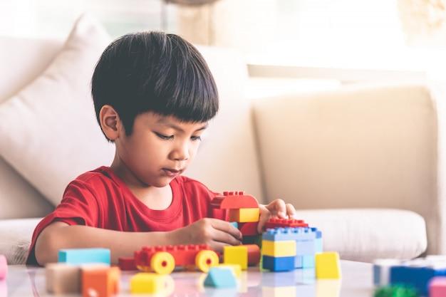 Ragazzo asiatico accatastamento blocchi giocattolo su un tavolo del salotto