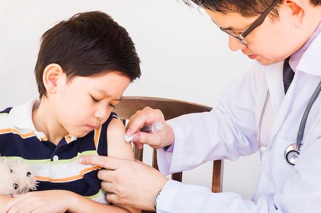 Ragazzo asiatico ammalato che è trattato dal medico maschio sopra priorità bassa bianca