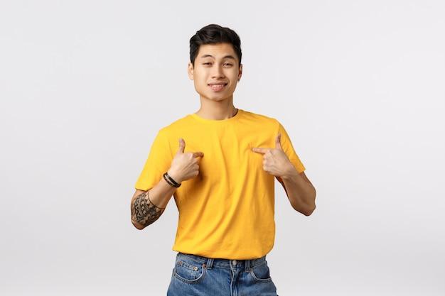 Ragazzo asiatico arrogante bello piacevole in maglietta gialla, indicando se stesso e sorridente, dipendente che promuove le proprie abilità, so che è esattamente chi ti serve, elogiando i tratti personali, muro bianco