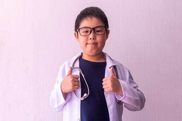 Ragazzo asiatico che gioca al dottore con lo stetoscopio in mani
