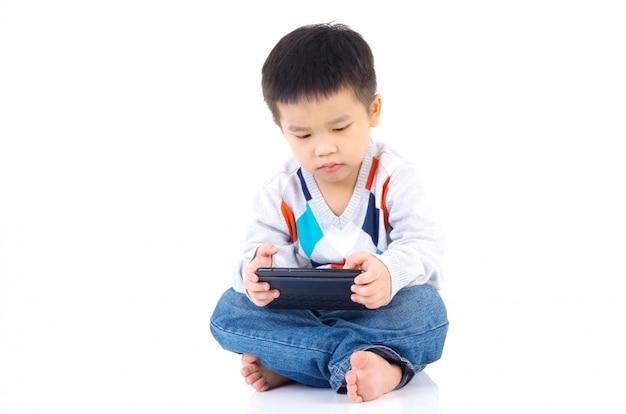 Ragazzo asiatico che gioca gioco sulla tavoletta digitale