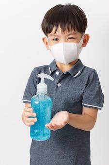 Ragazzo asiatico che indossa una maschera di protezione e che tiene la bottiglia del gel dell'alcool per le mani di pulizia.