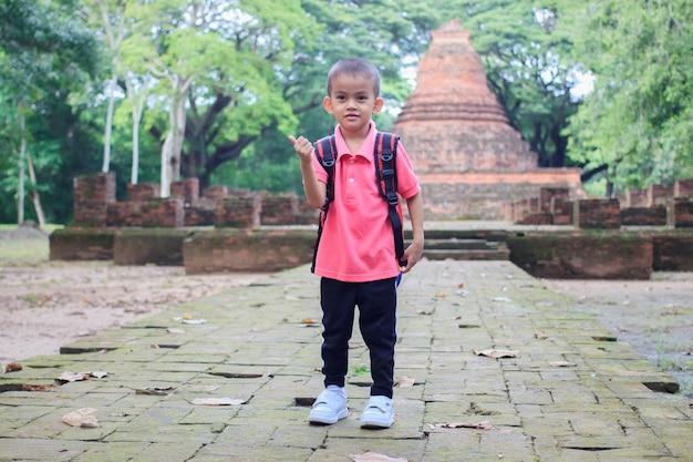 Ragazzo asiatico che sorride camminando alla città antica