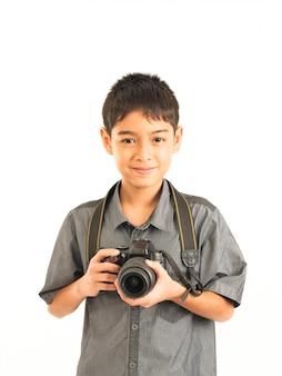 Ragazzo asiatico con la macchina fotografica di dslr su fondo bianco