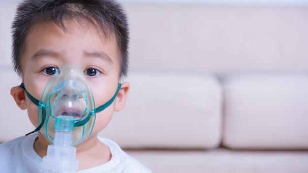 Ragazzo asiatico dei piccoli bambini del fronte del primo piano facendo uso dell'inalazione della maschera del nebulizzatore dell'inalatore di vapore con gli spcae della copia
