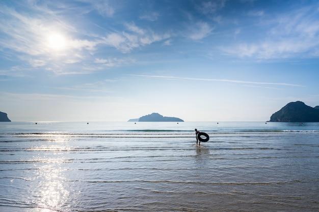 Ragazzo asiatico del bambino che gioca il mare a ao manao, mattina di estate, prachuap khiri khan, tailandia