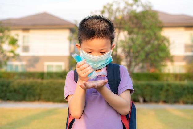 Ragazzo asiatico del bambino che utilizza il gel antisettico dell'alcool, prevenzione, pulizia delle mani frequentemente, prevenzione dell'infezione, scoppio di covid-19, ragazza lavarsi le mani con disinfettante per le mani dopo il ritorno da scuola.