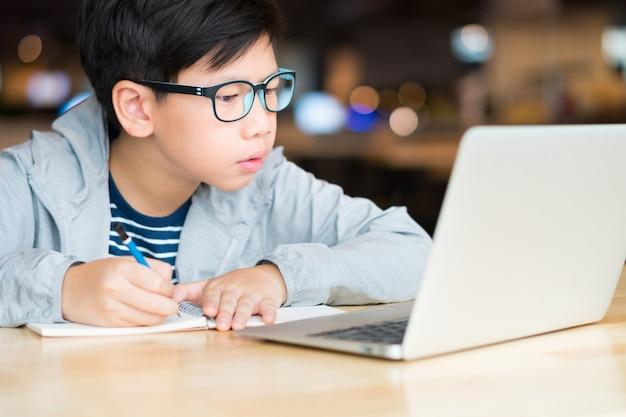 Ragazzo asiatico del preteen che sembra astuto che scrive e che per mezzo del computer portatile del computer che studia le lezioni online. ricerca, studio e risoluzione di problemi con concentrazione. apprendimento online e concetto di autoapprendimento.