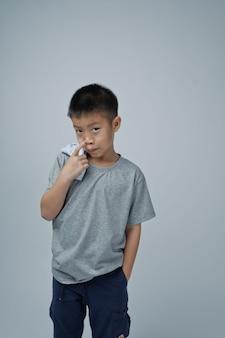 Ragazzo asiatico del ritratto su fondo grigio, studente tailandese, il bambino gode e felice