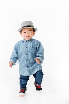 Ragazzo asiatico di un anno che sta e che sorride, tiro dello studio.