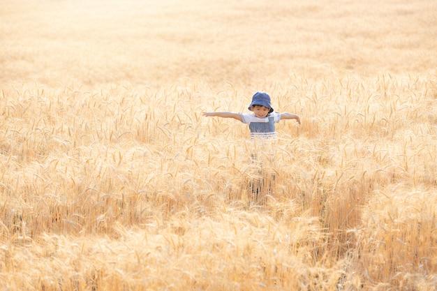 Ragazzo asiatico divertendosi e giocando in un campo di grano in estate.