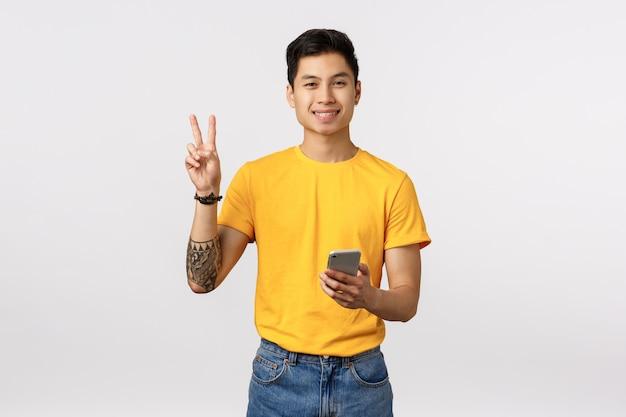 Ragazzo asiatico hipster carino e allegro con tatuaggi, mostrando il segno di pace e tenendo il telefono, sorridente gioioso, messaggistica, utilizzando l'applicazione, inviando positività durante il blog, muro bianco