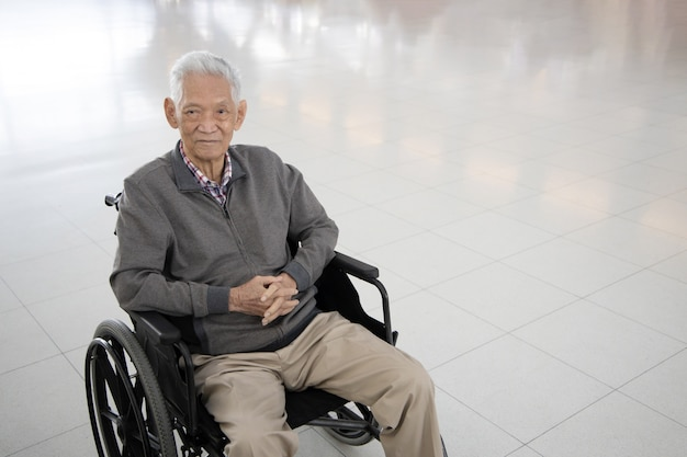 Ragazzo asiatico senior che si siede su una sedia a rotelle