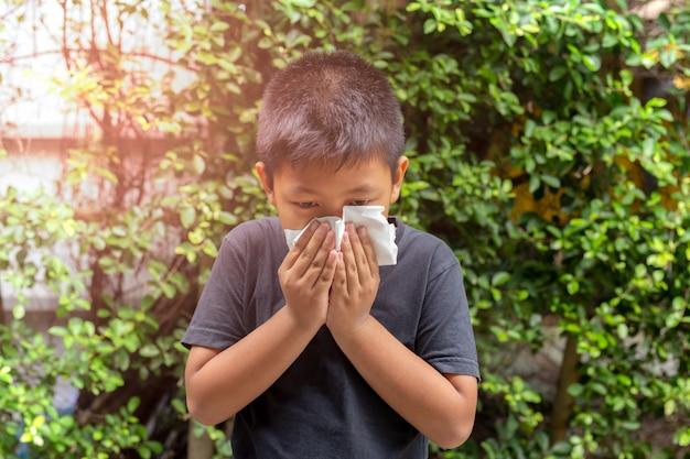 Ragazzo asiatico soffiarsi il naso con il tessuto, la stagione influenzale, la febbre da fieno.