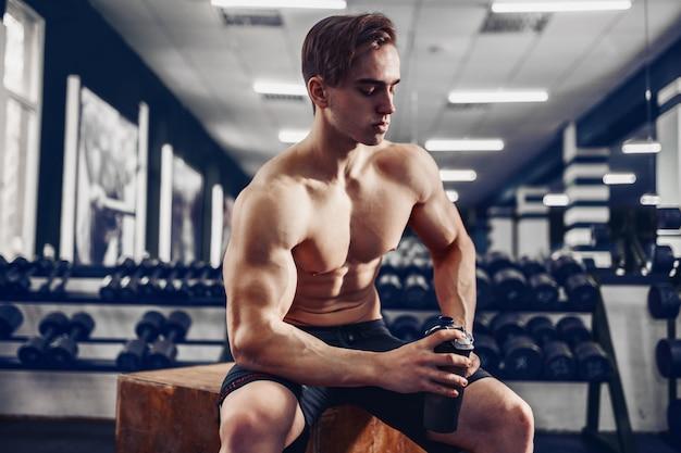 Ragazzo atletico molto potente, che si rilassa dopo il lavoro in palestra