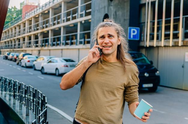 Ragazzo attraente alla moda hipster sta bevendo il caffè da una tazza di carta e parlando al telefono nel parcheggio vicino al supermercato.