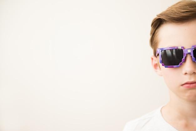 Ragazzo attraente serio in occhiali da sole sulla luce. metà del viso, copia dello spazio