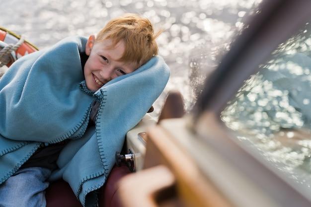 Ragazzo attraente sorridente di redhead su uno yacht.