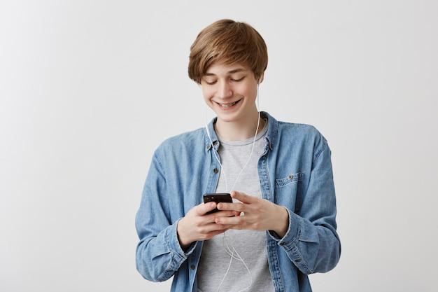 Ragazzo áucasico con capelli biondi in piedi contro uno sfondo grigio con smart phone che scarica musica usando la connessione internet cercando compiaciuto, eccitato, sorridente mentre guarda lo schermo del telefono cellulare