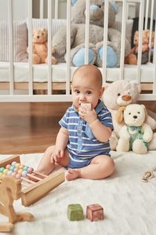 Ragazzo bambino gioca giocattoli di legno in una stanza per bambini in colori vivaci, camera da letto per bambini in stile scandinavo