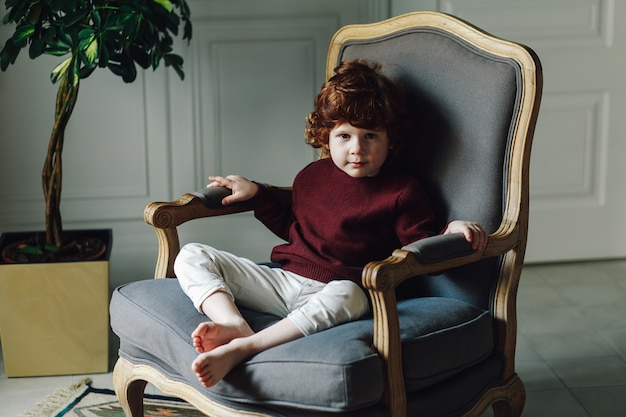 Ragazzo bambino in abiti casual in posa in poltrona