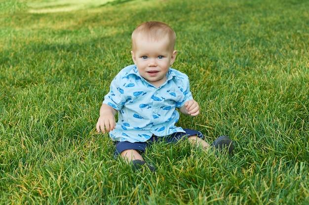 Ragazzo bambino sull'erba nel parco