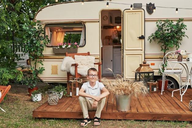 Ragazzo bambino vicino a una roulotte in estate al tramonto