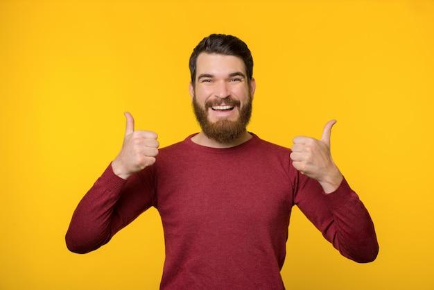 Ragazzo barbuto allegro, in piedi su sfondo giallo e mostrando il pollice in alto
