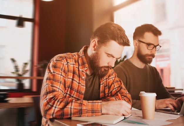 Ragazzo barbuto che annota le note sul suo taccuino mentre il suo amico sta leggendo un articolo al telefono. sono molto impegnati e concentrati.
