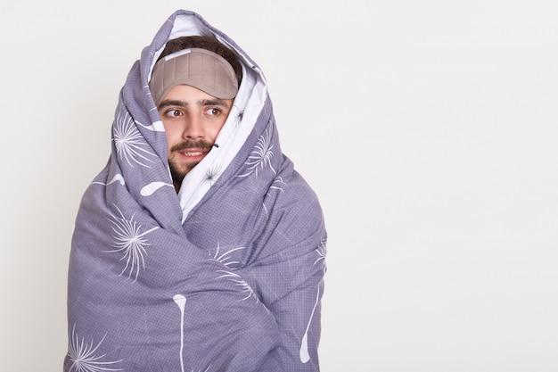 Ragazzo barbuto con la maschera per dormire sulla fronte che osserva da parte, essendo avvolto in una coperta, copia spazio pubblicitario o testo promozionale
