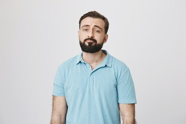Ragazzo barbuto cupo che sembra scettico e per nulla impressionato