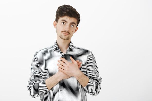 Ragazzo barbuto europeo in camicia a righe casual che tiene le mani sul cuore e sembra stanco, senza sentirsi preoccupato
