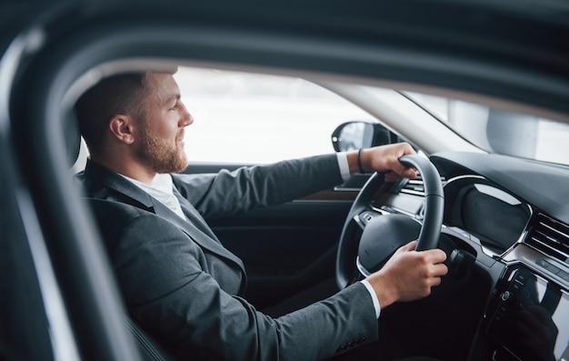 Ragazzo barbuto felice. uomo d'affari moderno che prova la sua nuova automobile nel salone dell'automobile