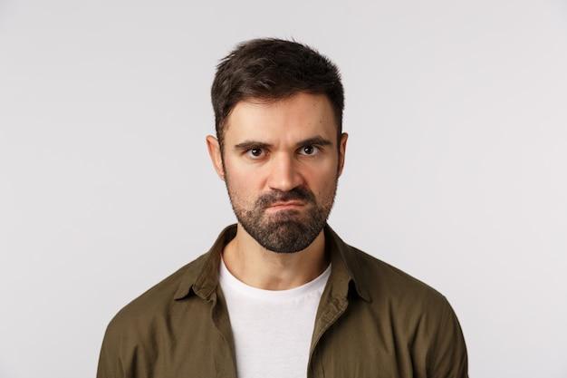 Ragazzo barbuto incazzato arrabbiato che perde la pazienza, vuole uccidere qualcuno, fissando aggressivo, cercando di tenere la bocca chiusa e non colpire la persona come sensazione di rabbia e aggressività, succhiare le labbra, accigliato fissando con disprezzo