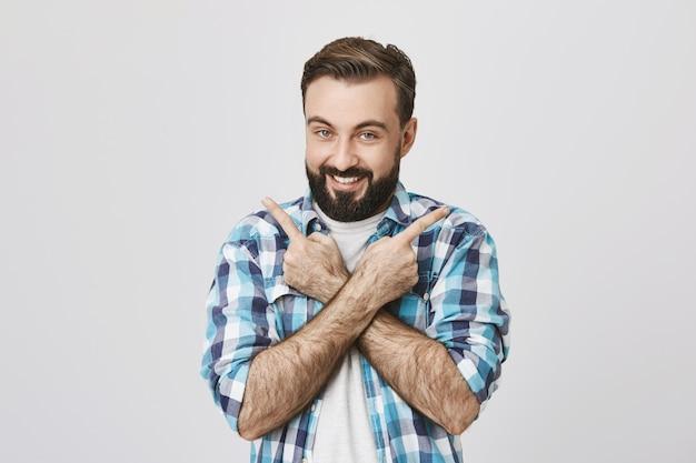 Ragazzo barbuto sorridente che mostra i prodotti, indicando lateralmente