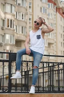 Ragazzo bello biondo uomo hipster in eleganti abiti estivi in strada