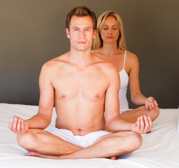 Ragazzo bello che fa gli esercizi sul letto con sua moglie
