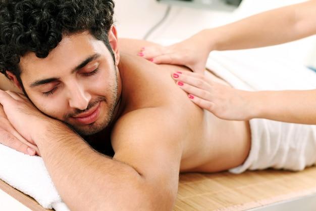 Ragazzo bello che gode della terapia di massaggio