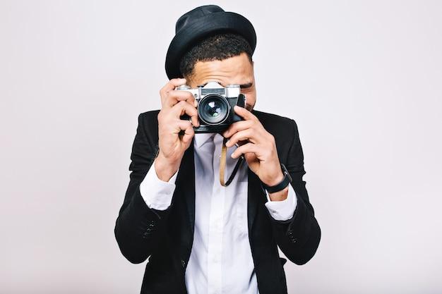 Ragazzo bello eccitato ritratto in vestito che fa foto sulla macchina fotografica. divertirsi, godersi il viaggio, turista, isolato, sorridente, felicità.